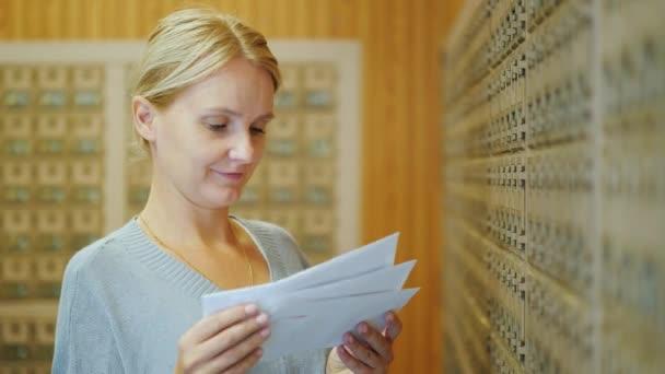 Atraktivní žena vypadá prostřednictvím dopisů v poště na pozadí poštovních schránek