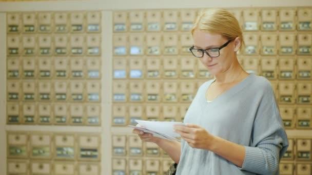 Žena se dívá na dopisy právě obdrželi. Mělo by být v poště na pozadí poštovních schránek