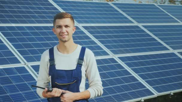 Porträt eines jungen Arbeiters in Arbeitskleidung, der lächelt und in die Kamera blickt. vor dem Hintergrund von Sonnenkollektoren