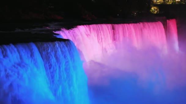 The colorful Niagara Falls at dusk, brightly illuminated by spotlights