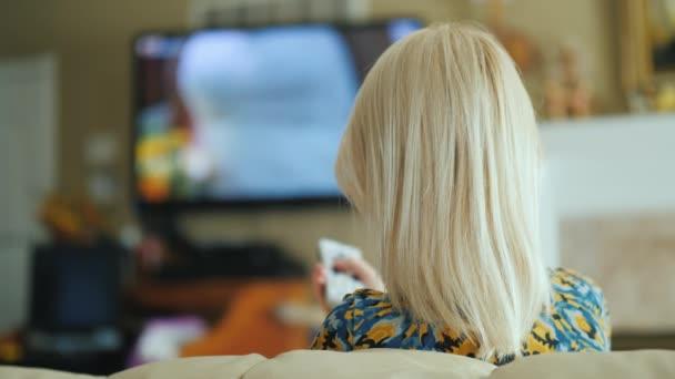 Žena se dívá na televizi v obývacím pokoji, pohled zezadu. Obsahuje dálkové ovládání