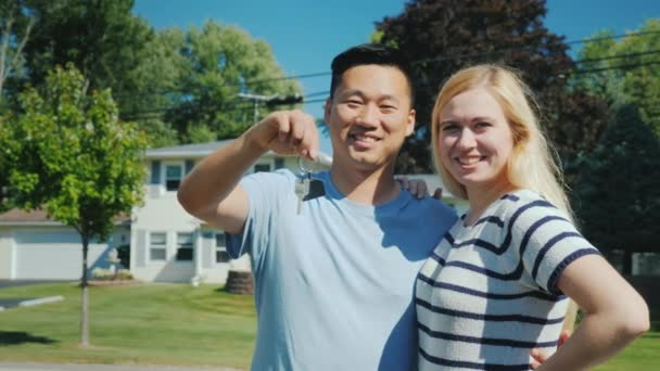 Happy multi-ethnic couple on the background of their new home. Holds a key chain with keys in hand. Buying real estate concept