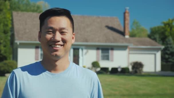 Portrét šťastný Asiat na pozadí nového domova. Při pohledu na fotoaparát, s úsměvem. Úspěšný nákup nemovitostí koncepce