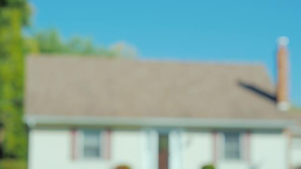 Muž a žena držet ruce na pozadí dům svých snů. Jen ruce jsou zobrazeny v rámečku.