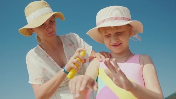 Mom puts sunscreen on the skin of her daughter. Rest and sun protection