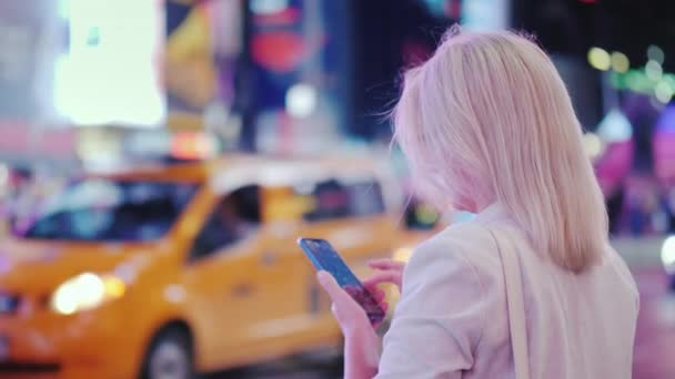 Rückansicht: Geschäftsfrau nutzt Smartphone am geschäftigen Times Square in New York. die berühmten gelben Taxis fahren vorbei - das Symbol der Stadt.