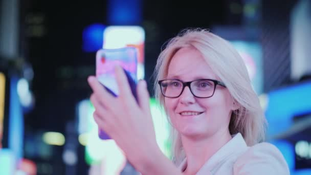 Portrait of an attractive woman taking pictures of sights in Times Square. It stands on the background of blurry advertising lights