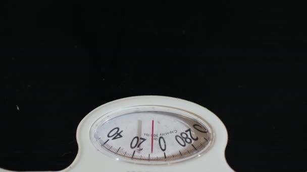 Muž měří váhu na mechanické podlahové váhy. Detail videa