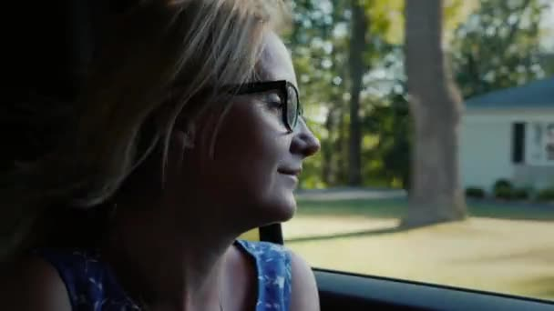 A woman rides in the car at the passengers place, looks in the open window with a typical US suburb