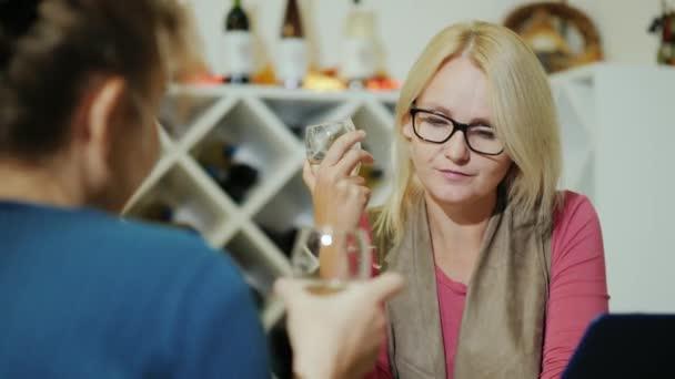 Dvě ženy, degustace vína v kavárně či vinařství. Sedni si ke stojanu s lahví, používání notebooku