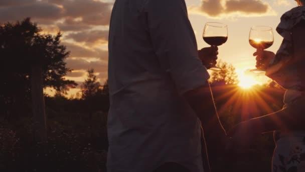Romantische Paare halten Händchen und klirren Gläser mit Wein bei Sonnenuntergang.