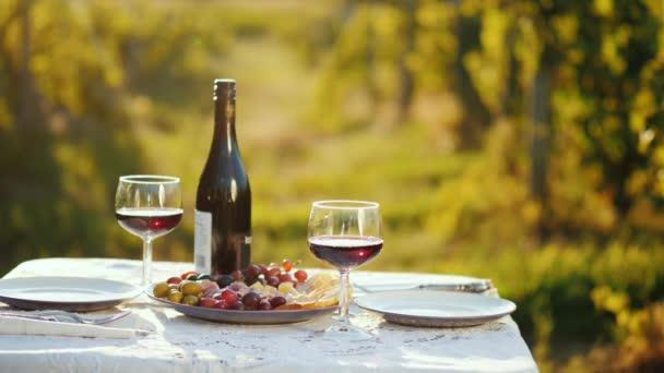 Láhev vína s občerstvením je na stole. Na pozadí rozostřené obrysy vinice. Místo pro romantickou večeři