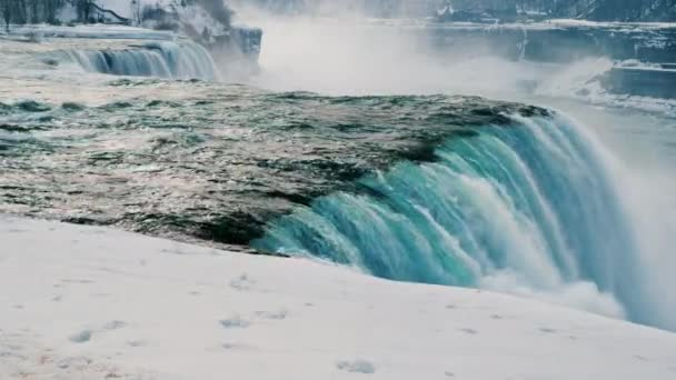 Winter at Niagara Falls. Streams of water flow surrounded by snow-covered shore.