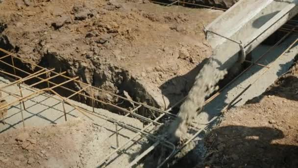 Ready concrete flows through the pipe into the foundation  Working vibrator  compacts it