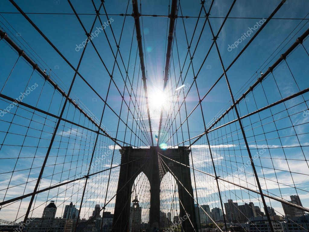 The silhouette of the famous Brooklyn Bridge, the sun at its zenith shines above its pillars. One of the most famous symbols of New York