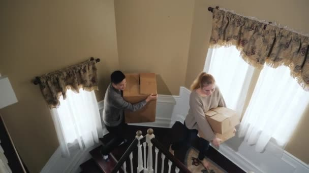A multiethnic couple climbs the stairs, carries cardboard boxes in their hands. Moving to a new house or housewarming concept. Slow motion video