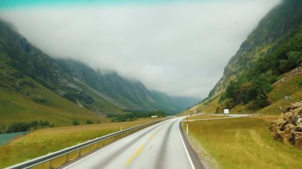 Malebná silnice mezi horami v Norsku. Pohled z okna cestovní auta
