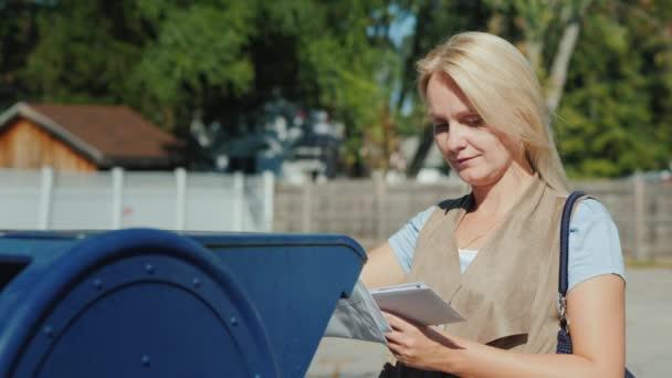Eine Frau betrachtet die Umschläge mit Briefen, wirft sie dann in den blauen Briefkasten auf der Straße