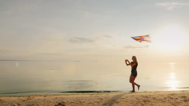 Bezstarostné mladá žena běží na pláži s drakem. Na pozadí krásného západu slunce obloha