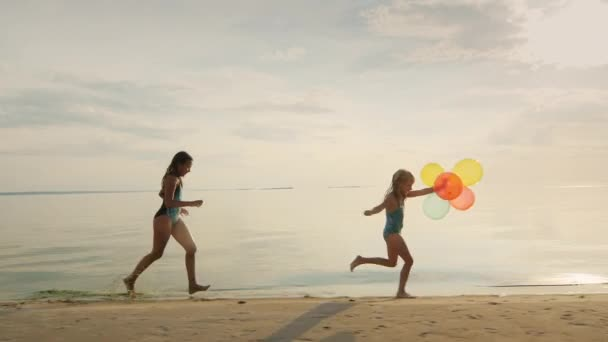 Two sisters playing together on the beach. One girl runs after another, holding balloons