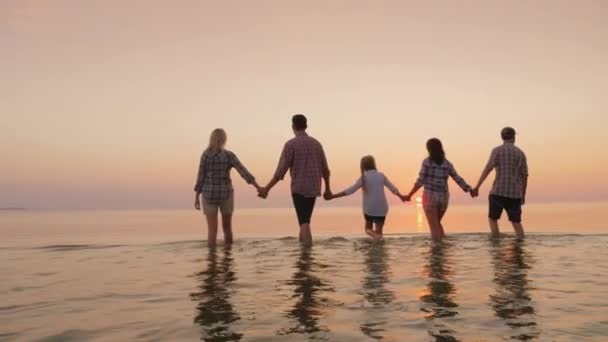 Parents with children have fun in the water. Beautiful sunset over the sea
