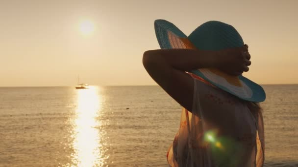 Romantic woman in a hat admires the sunrise over the sea, the ship is far away