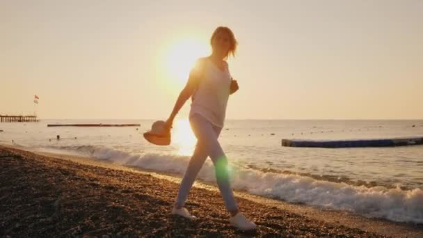A happy woman walks carefree along the surf line, the sun rises over the sea. Holiday and vacation concept, escape from problems and fuss