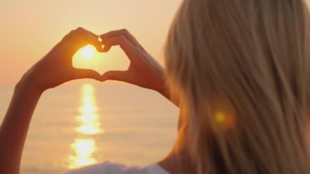 Eine junge Frau hält Händchen in Herzform über dem Meer. es gibt eine aufgehende Sonne. Liebe und Hoffnung, freuen Sie sich auf das Konzept