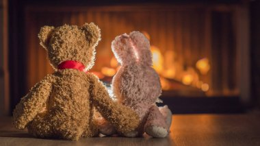 Toy bear hugging a hare look at the burning fireplace