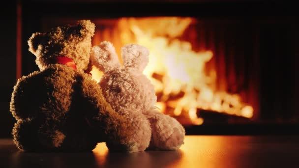 Két barát, egy nyúl és egy medve sütkérezik a kandalló mellett. Ölelés - barátság és kényelem a házban