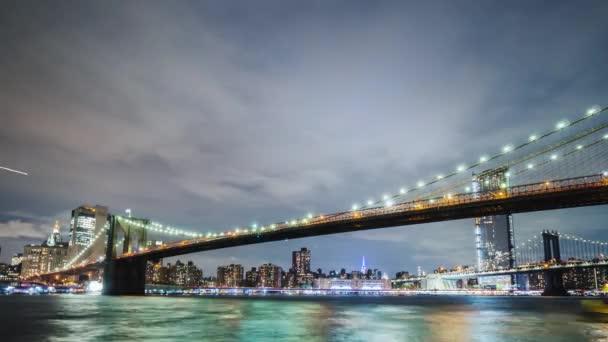 Dva nejznámější mosty v New Yorku jsou Brooklynský most a Manhattan Bridge. Na pozadí noci panoráma. Širokoúhlý záběr