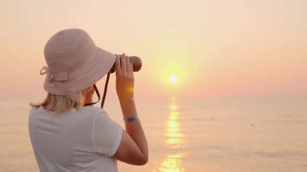 A young traveler in a hat looks through binoculars to the pink sea, where the sun rises. Romance and adventure concept