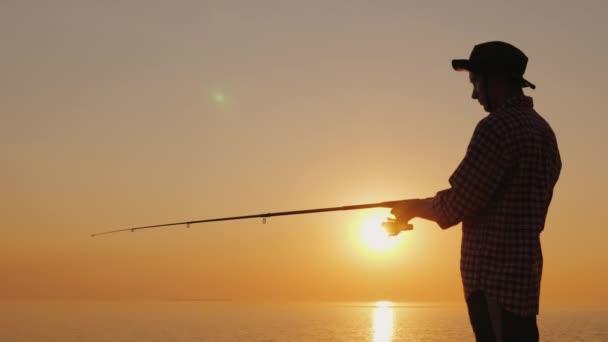 Silueta mladý rybář loví na pláži při západu slunce. Boční pohled