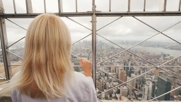Rückansicht einer Frau, die New York City von einem Höhepunkt aus bewundert