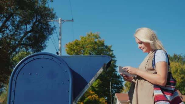 Eine junge Frau schickt einen Brief in der Post, legt es in den Briefkasten auf der Straße