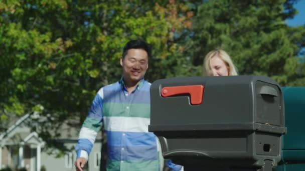 Ein junges Paar holt Post aus einem Briefkasten in der Nähe des Hauses