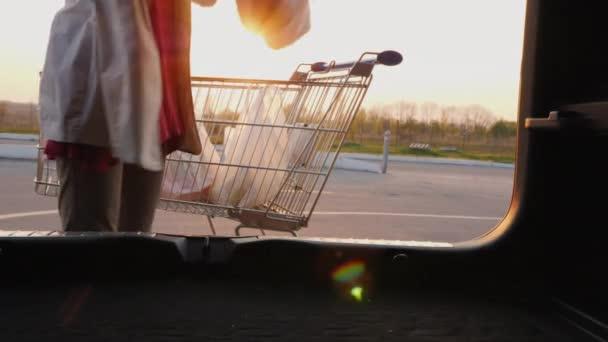 Žena dává nákupní tašky do kufru auta. Pohled zevnitř auta