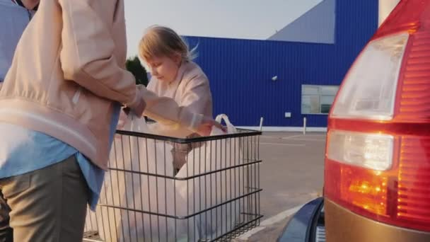Family unload shopping carts in the trunk of a car, side view