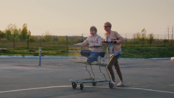 Mutter rollt Tochter in Einkaufskorb
