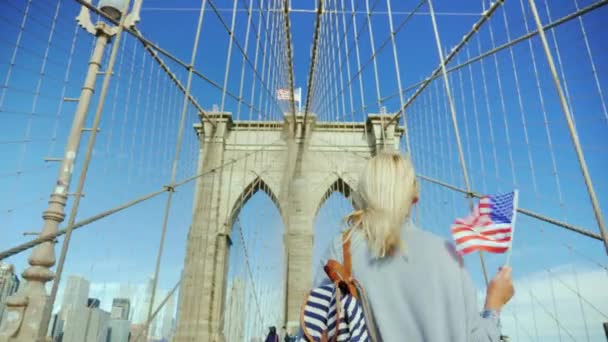 A tourist walks on the Brooklyn Bridge, holds the flag of America in his hand