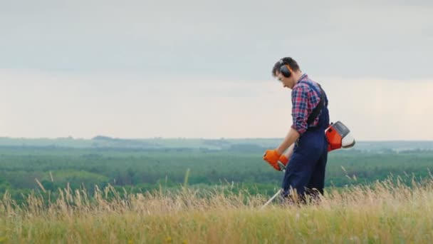 A man mows thick grass with a trimmer. In a picturesque place