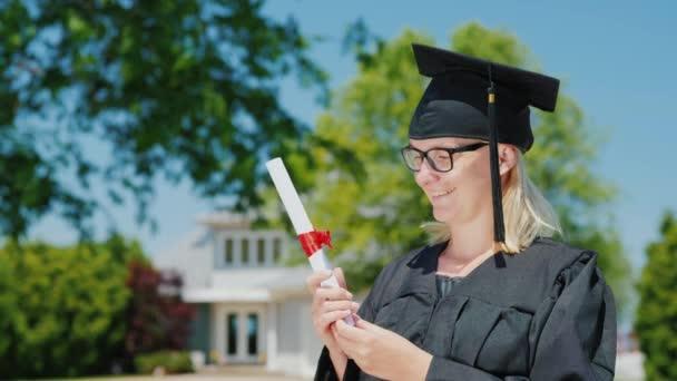 Portrét ženy v plášti a v čepici s promokou, držící v ruce diplom na pozadí jejího domu