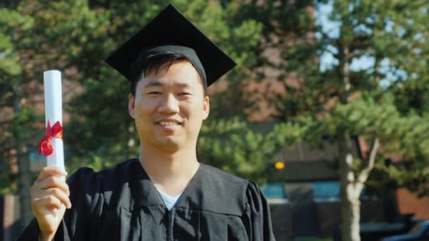 Portrait of an Asian man in graduate clothes. College graduation concept