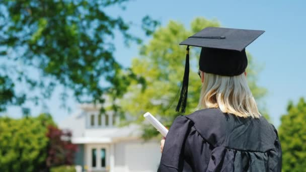 Pohled na ženu v plášti a v čepici s promokou, držící v ruce diplom na pozadí jejího domu
