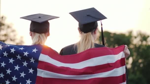 Dva absolventi vysokých škol s americkou vlajkou. Zadní pohled