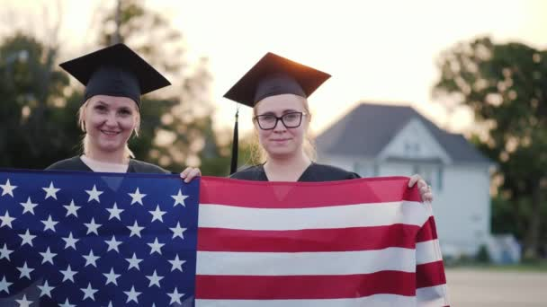 Two college graduates in gowns and caps with the American flag