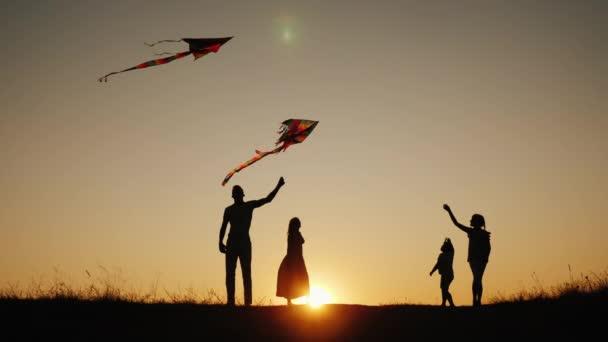 La famiglia attiva con i bambini lancia aquiloni in un luogo pittoresco al tramonto