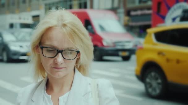 Atraktivní žena v brýlích se dívá na obrazovku smartphone. na pozadí s těžkou dopravou. Manhattan, New York