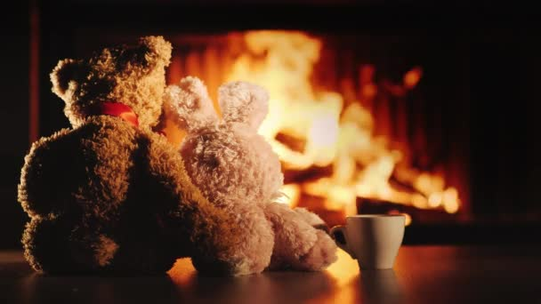 Tea by the fireplace. Two friends bear and hare look at the fireplace, next to a cup of tea