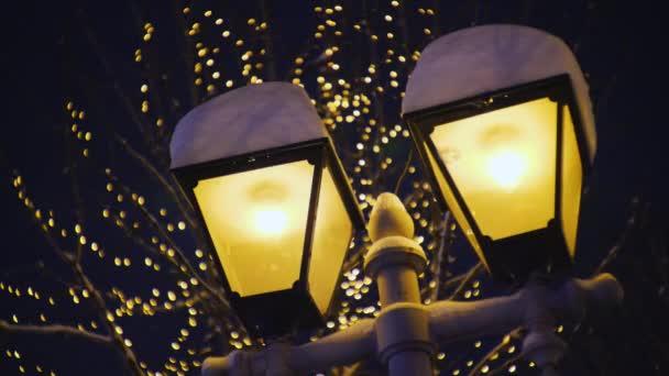 Lampen auf einem Laternenpfahl mit Schnee bedeckt, Straßenbeleuchtung an einem Winterabend, verschneites Wetter